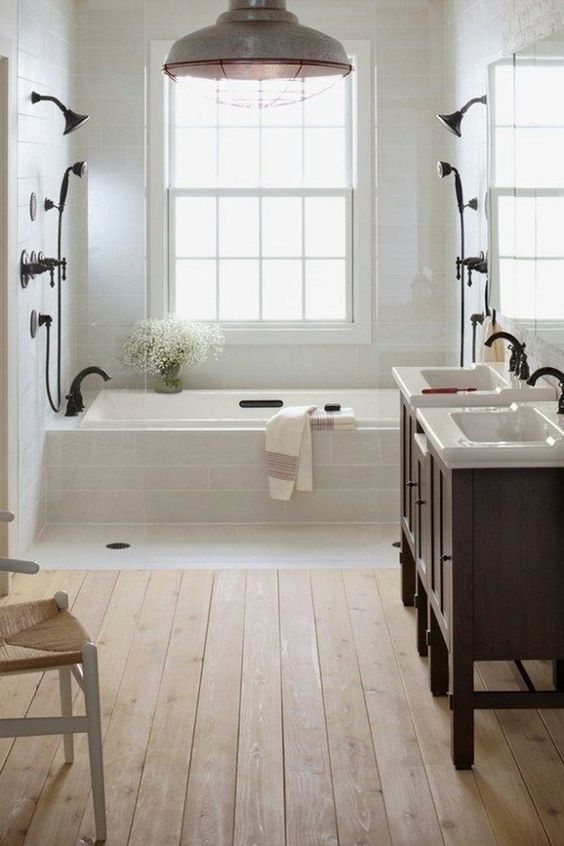 a light-filled farmhouse bathroom with a wooden floor, white tiles, dark wooden vanities and black fixtures