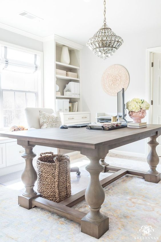 a light filled farmhouse home office with a large wooden desk, neutral storage units, a crystal chandelier and neutral blooms