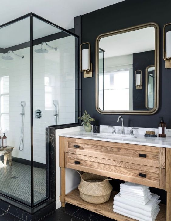 a modern farmhouse bathroom with a stained vanity, a mirror in a metal frame, a shower and black walls and floor