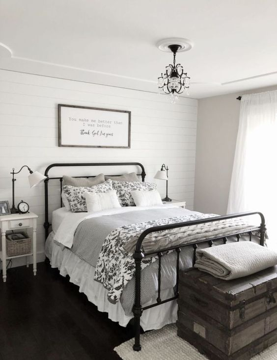 a modern farmhouse bedroom in a monochromatic color scheme, with much grey and printed textiles