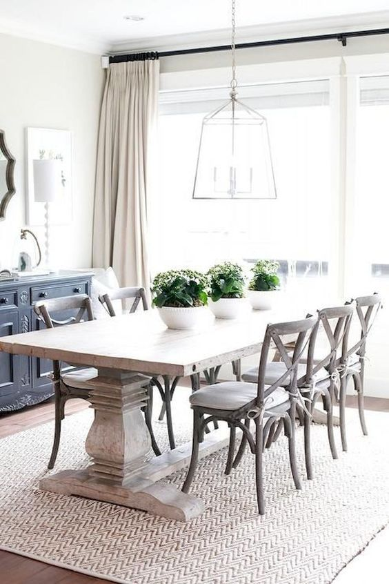 a modern farmhouse dining room with a whitewashed table, white chairs, a frame lamp and a buffet
