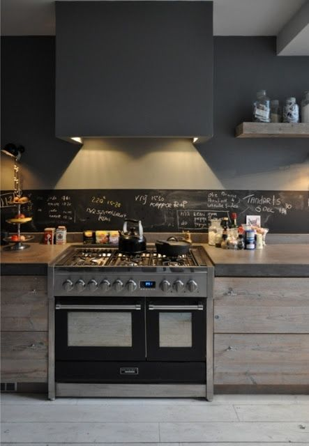 a modern industrial space with a small chalkboard backsplash and lights looks very rough and masculine, still rather inviting