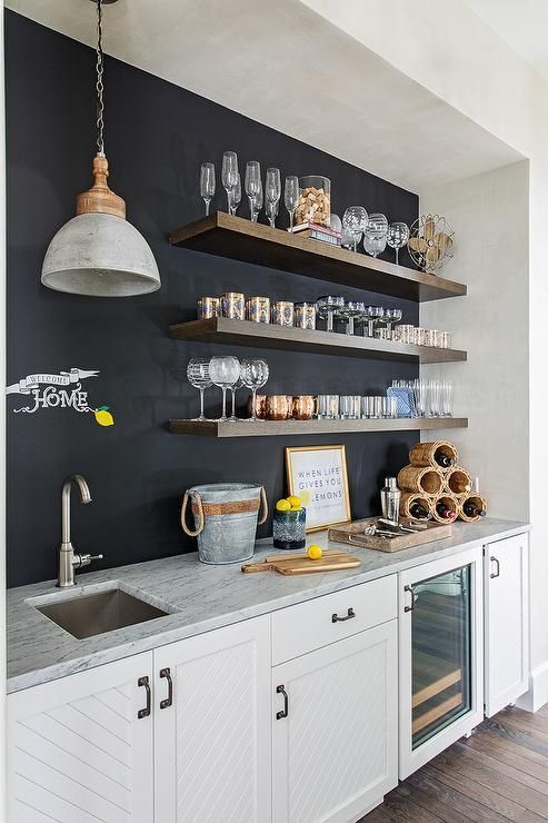 a modern neutral kitchen with a chalkboard wall, open shelving and a pendant lamp is a stylish and cool space