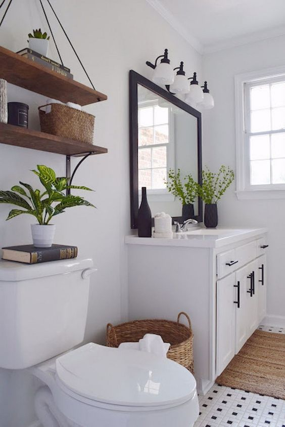 a modern white farmhouse bathroom with a modern vanity, a dark framed mirror, stained shelves and much light