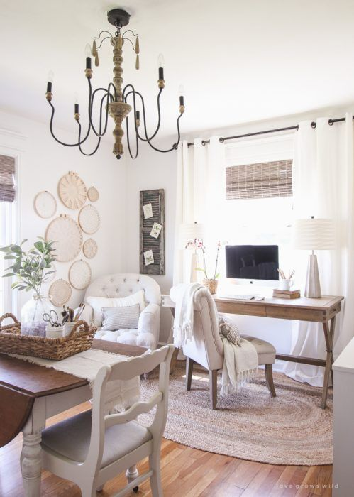 a neutral and cozy farmhouse home office with a wooden desk and a table, neutral upholstered chairs, a vintage chandelier, macrame art on the wall