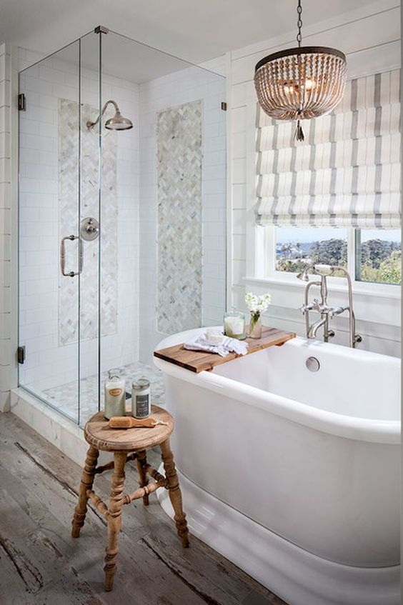 a neutral farmhouse bathroom with marble tiles, Roman shades, a bead chandelier and a vintage wooden stool