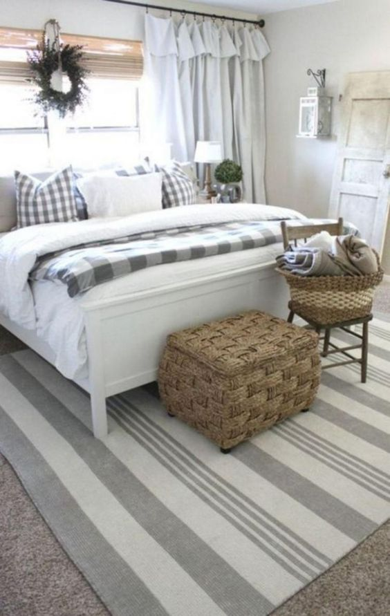 a neutral farmhouse bedroom with checked and striped textiles, a wicker chest and greenery