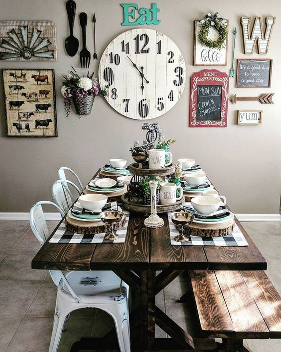 a neutral farmhouse dining area spruced up with a bright gallery wall, with a stained table and bench plus white metal chairs