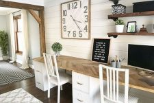 a neutral farmhouse shared home office with a pretty wood clad desk, industrial shelves, a large clock and some white chairs