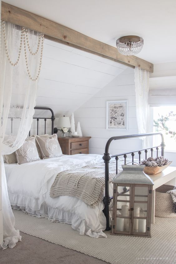 a neutral farmhouse space with a wooden beam with beads and curtains, a large candle lantern and neutral textiles