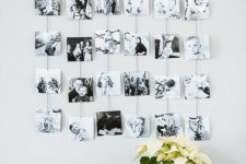 a photo display with a wooden rail and black and white photos on yarn hanging down is a lovely idea