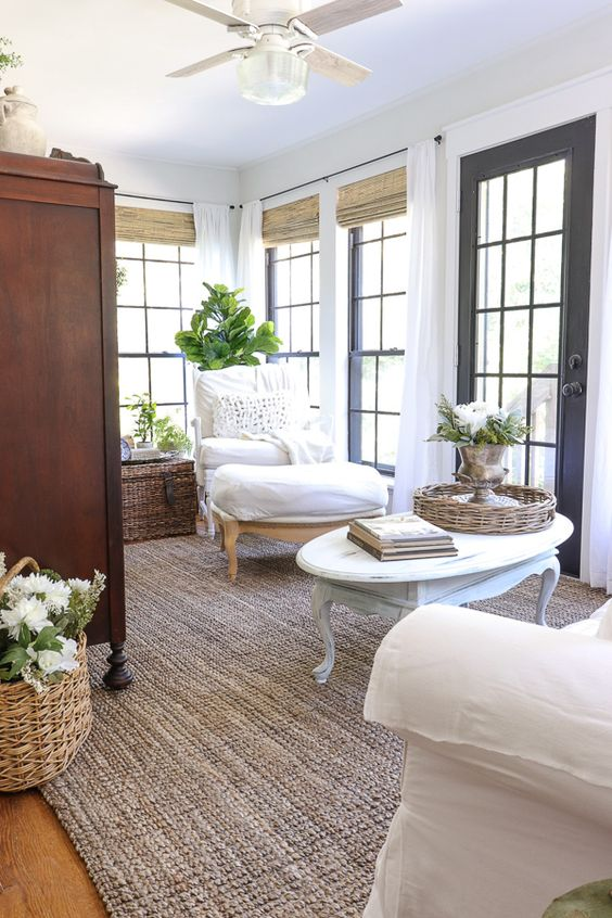 a refined farmhouse sunroom with elegant neutral furniture, baskets and chests, potted greenery and blooms and shades