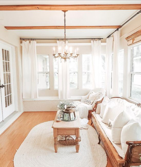 a refined neutral French farmhouse sunroom with elegant furniture, a wooden table, greenery, a vintage chandelier and wooden beams on the ceiling