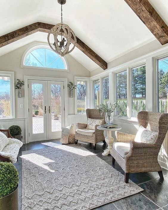 a rustic sunroom with wooden beams, elegant rattan and wooden furniture, a rug, pillows and potted greenery