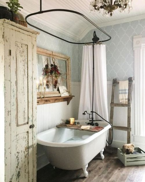 a shabby chic farmhouse bathroom with grey printed wallpaper, a white clawfoot tub, a shabby chic storage unit, a mirror in a wooden frame