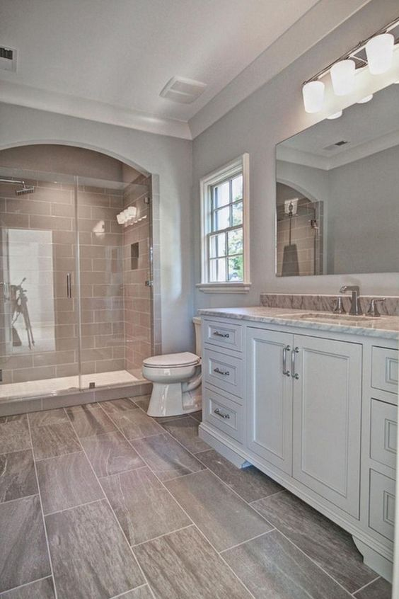 a simple and neutral farmhouse bathroom with a white vanity, brown marble tiles, taupe tiles in the shower