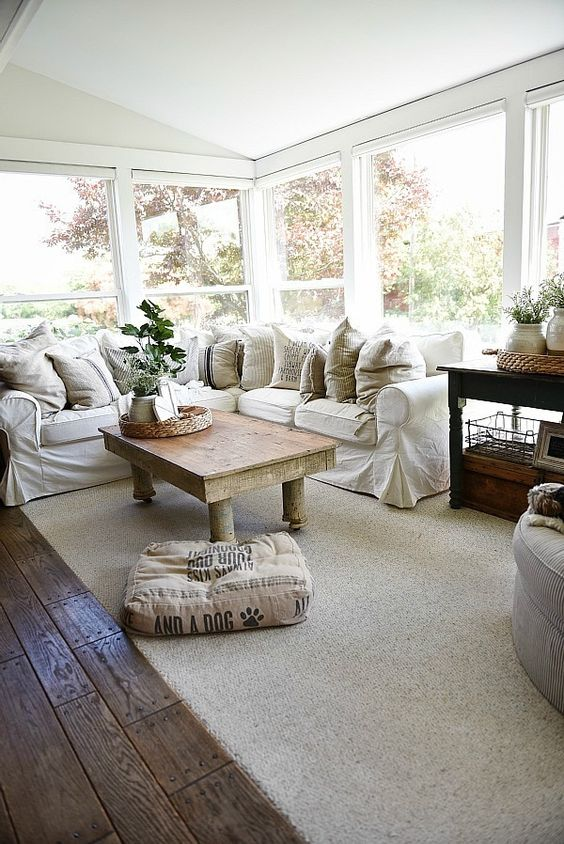 a simple farmhouse sunroom with an L shaped white sofa, potted greenery, a rustic table and neutral textiles