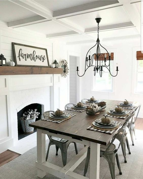 a simple modern farmhouse dining area with a white fireplace, signs and pumpkins, a wooden table and metal chairs