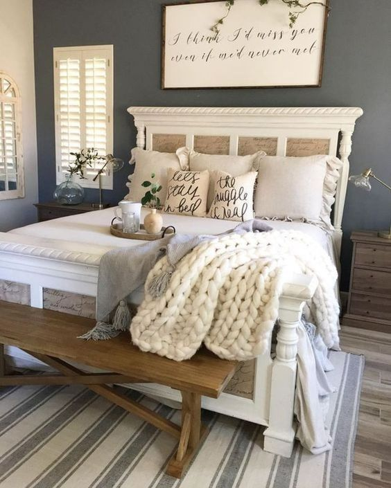 a stylish farmhouse bedroom with blue walls, striped textiles, knit and burlap accessories and a wooden bench