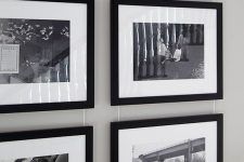 a stylish gallery wall with photos in black frames hanging on wire from above is a chic decor idea
