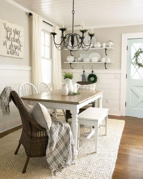 a traditional farmhouse dining nook with open shelves, a wooden table, wooden and wicker chairs and a metal chandelier