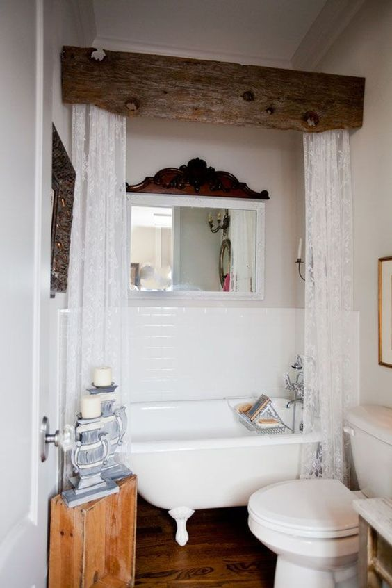 a vintage farmhouse bathroom in white, with dark wooden touches for an accent, a tree stump side table and a clawfoot bathtub