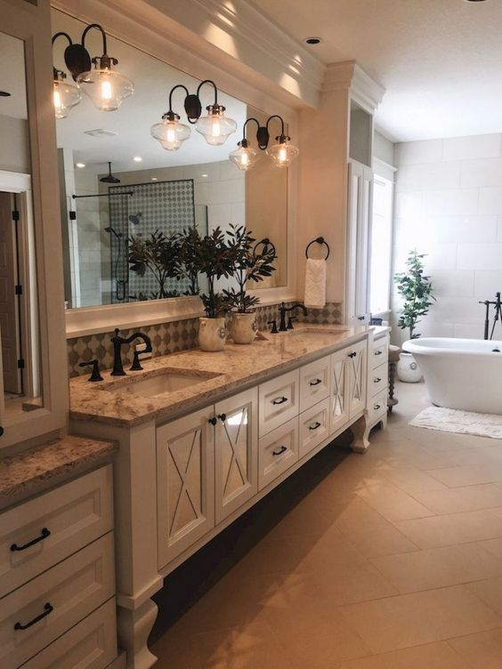a vintage farmhouse bathroom with a large creamy vanity, vintage lamps and storage units plus a modern tub