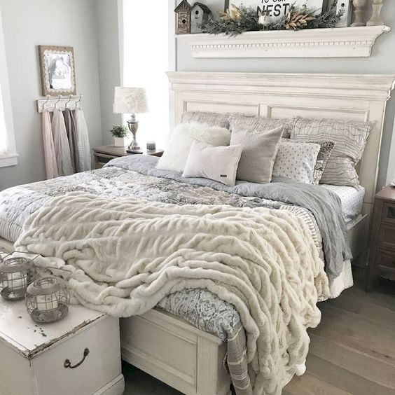 a vintage farmhouse bedroom done in neutrals, with vintage furniture and soft textural textiles