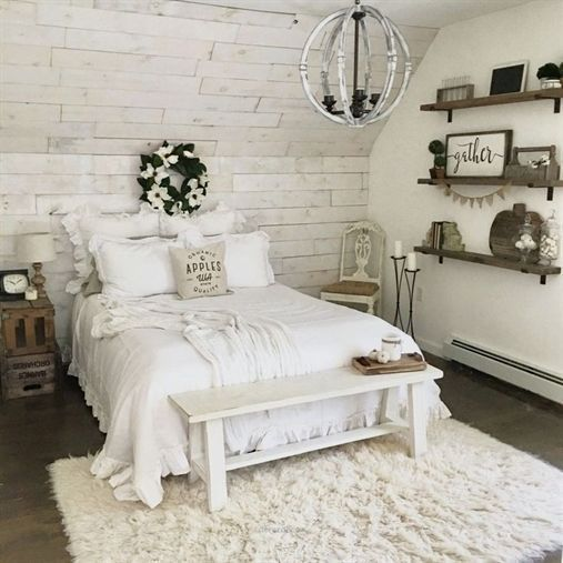 a vintage farmhouse bedroom of whitewashed wood, with elegant furniture and  a metal chandelier