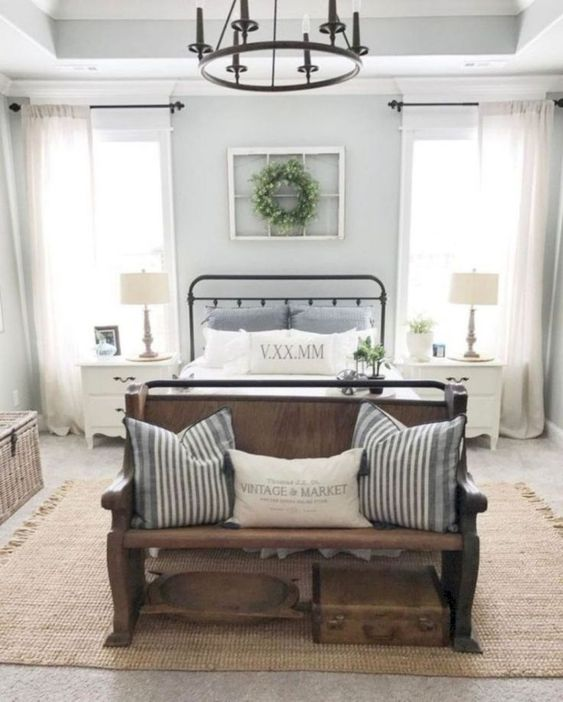 a vintage farmhouse bedroom with a metal chandelier, a wooden bench and striped textiles