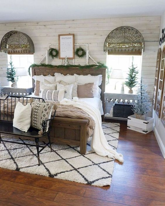 a vintage farmhouse bedroom with wooden furniture, a vintage bench, a rustic wooden bed and neutral textiles