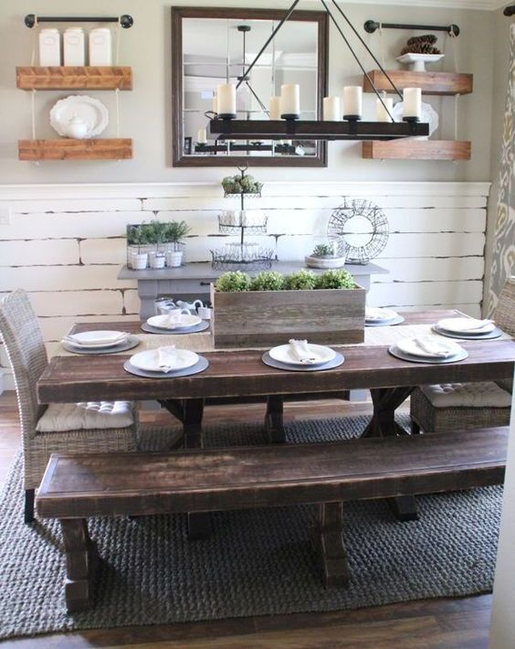 a vintage farmhouse dining area with a whitewashed wall, shelves, dark stained wooden dining set and a wooden chandelier
