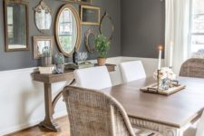 a vintage farmhouse dining area with wicker and upholstered chairs, a wooden table and a gallery wall with frames and mirrors