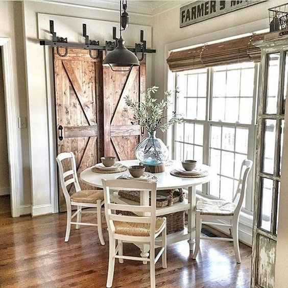 a vintage farmhouse dining nook with wooden doors, a white dining set, wicker shades and a metal lamp