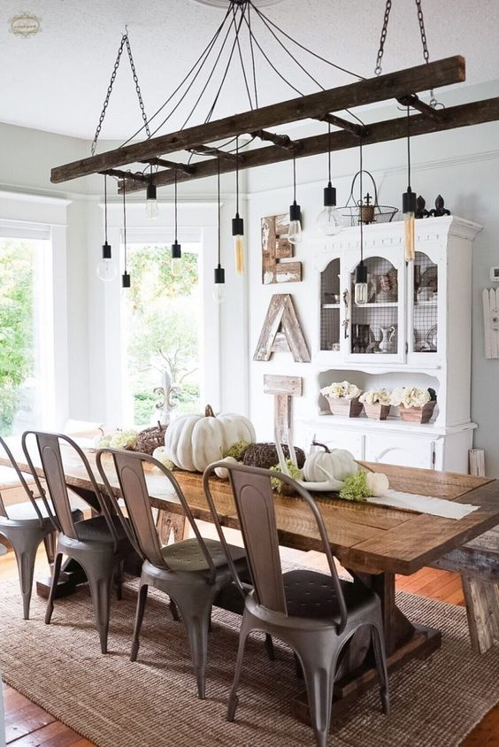 a vintage farmhouse dining room with a white buffet, a wooden sign, a ladder with bulbs, a wooden table and metal chairs