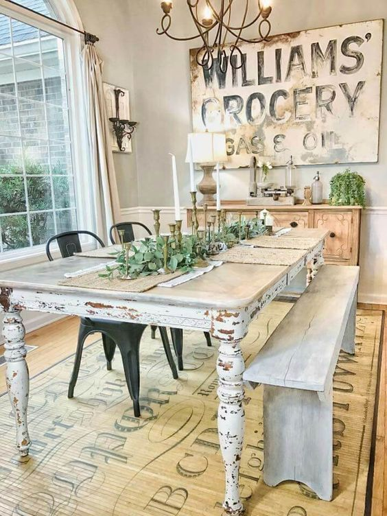 a vintage farmhouse dining space with a large sign, a wooden buffet, a shabby chic table and whitewashed bench