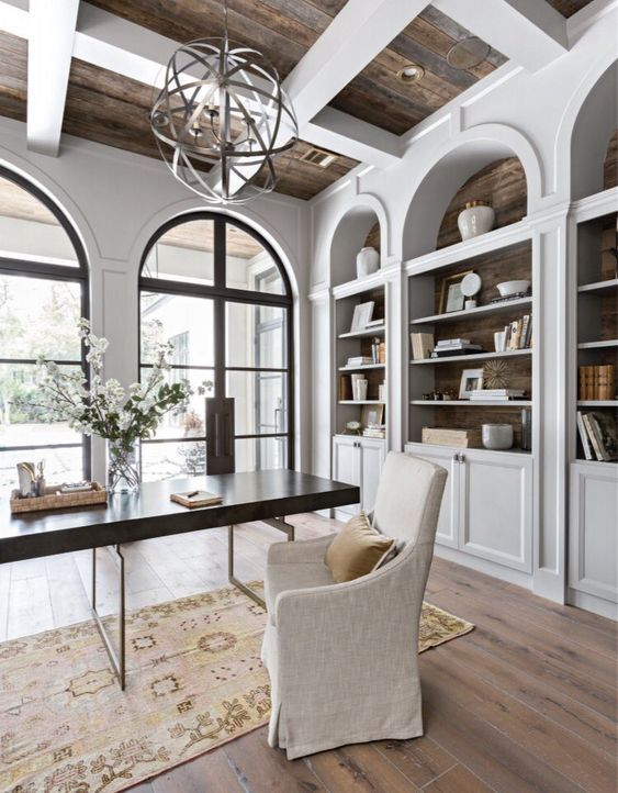 a vintage farmhouse home office with white walls and storage units, a sphere chandelier, a modern desk and an upholstered chair