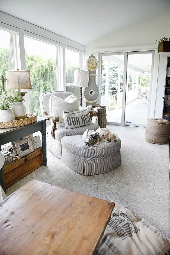 a vintage farmhouse sunroom with vintage rustic furniture, a striped lounger, lamps, greenery and a clock in neutrals