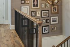 a vintage-inspired gallery wall with photos in mismatching frames over the staircase is a cozy decor idea