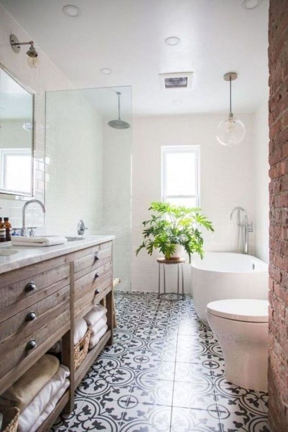 a welcoming farmhouse bathroom with a stained vanity, a brick wall, a mosaic tile floor and an oval tub