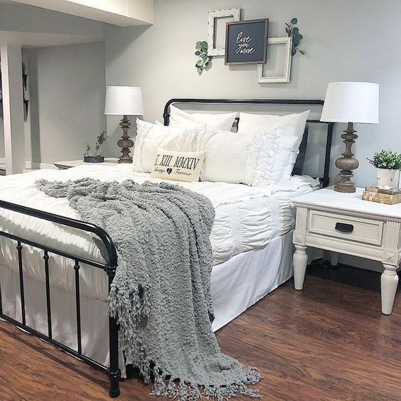 a welcoming farmhouse bedroom in neutrals and a black metal bed plus artworks over the bed