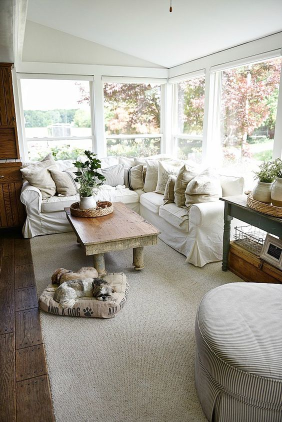 a welcoming farmhouse sunroom with a white L shaped sofa, some vintage tables, baskets, neutral textiles and potted greenery