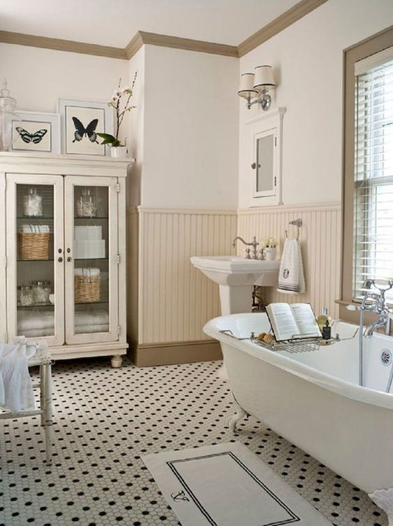 a welcoming neutral bathroom with penny tiles on the floor, sady beadboard, a clawfoot tub and a glass armoire for storage