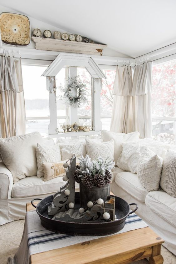 a welcoming neutral farmhouse sunroom with a sectional, vintage decor, wreaths, clocks and textiles in creamy shades