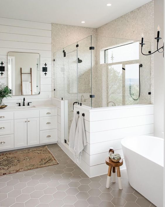 a white farmhouse bathroom with plank walls, grey hex tiles, an oval tub, a vintage vanity and touches of black
