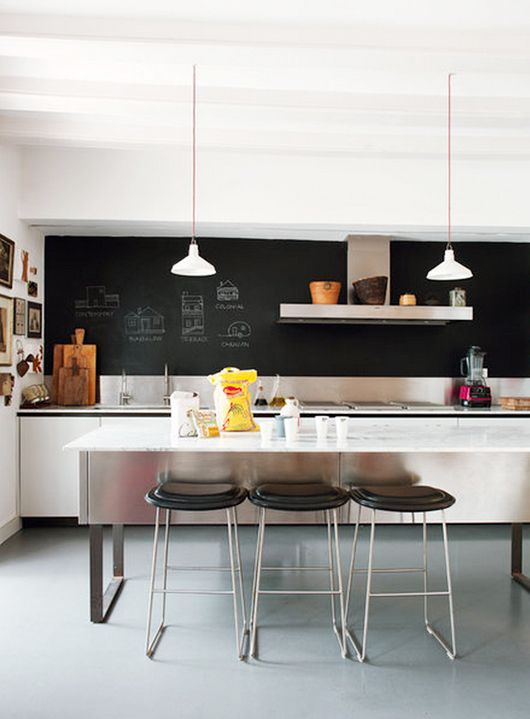 a white minimalist kitchen with a chalkboard wall plus a tiny metal backsplash is a stylish space with no excessive decor