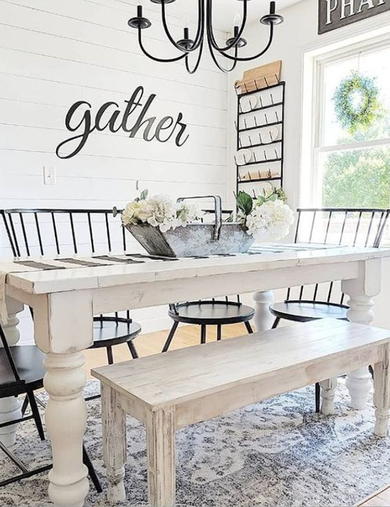 an airy and welcoming farmhouse dining room with a white dining set, black chairs, a black chandelier and much light