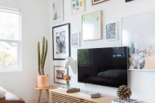 an eclectic gallery wall with bright photos and mismatching frames all over the wall is cool and bold