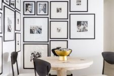 an elegant black and white gallery wall with matching black frames creating a mood in the dining nook