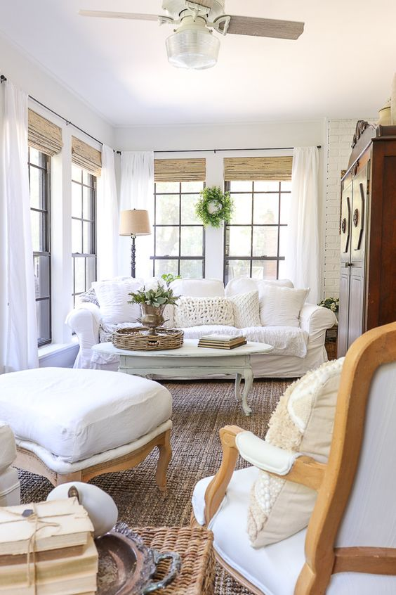 an elegant vintage farmhouse sunroom with white furniture, a chalk painted table, greenery and shades